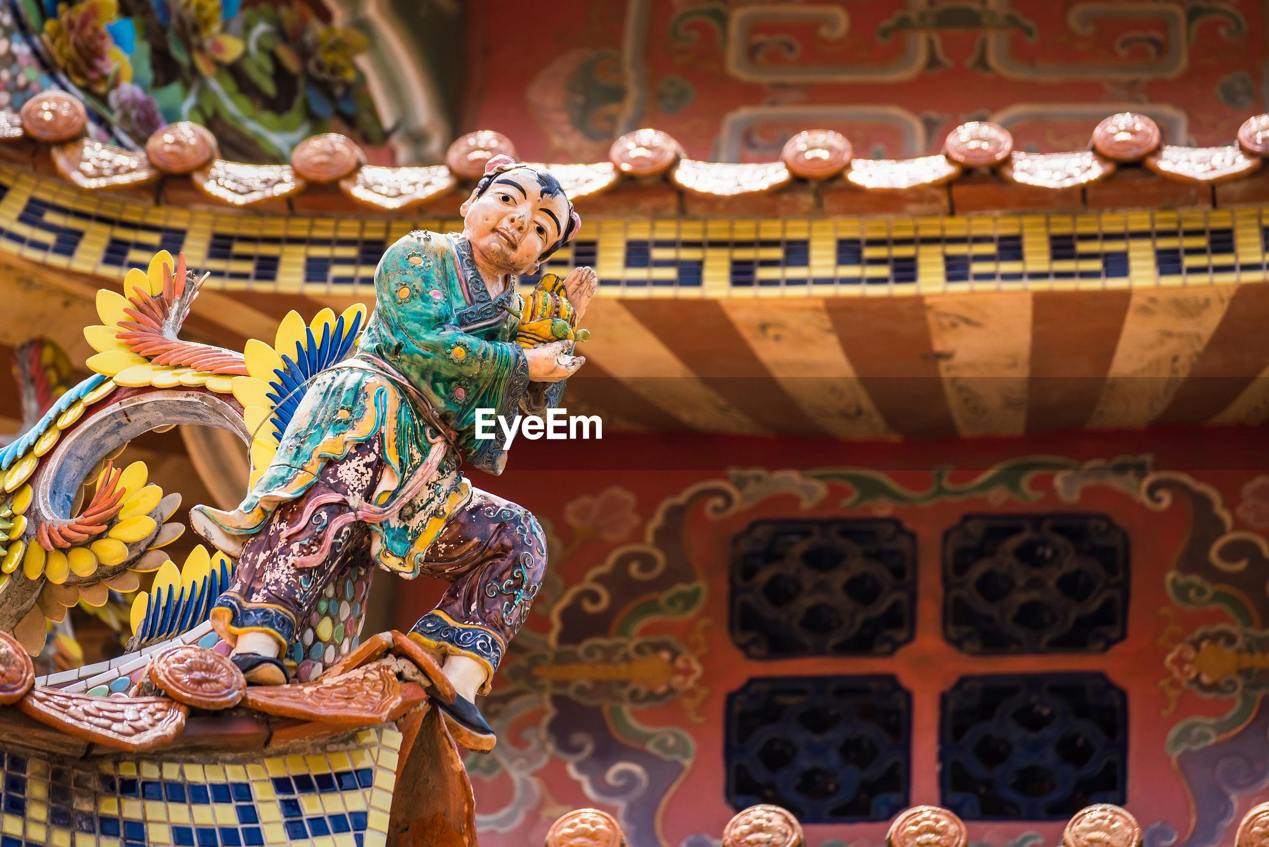Statue against buddhist temple