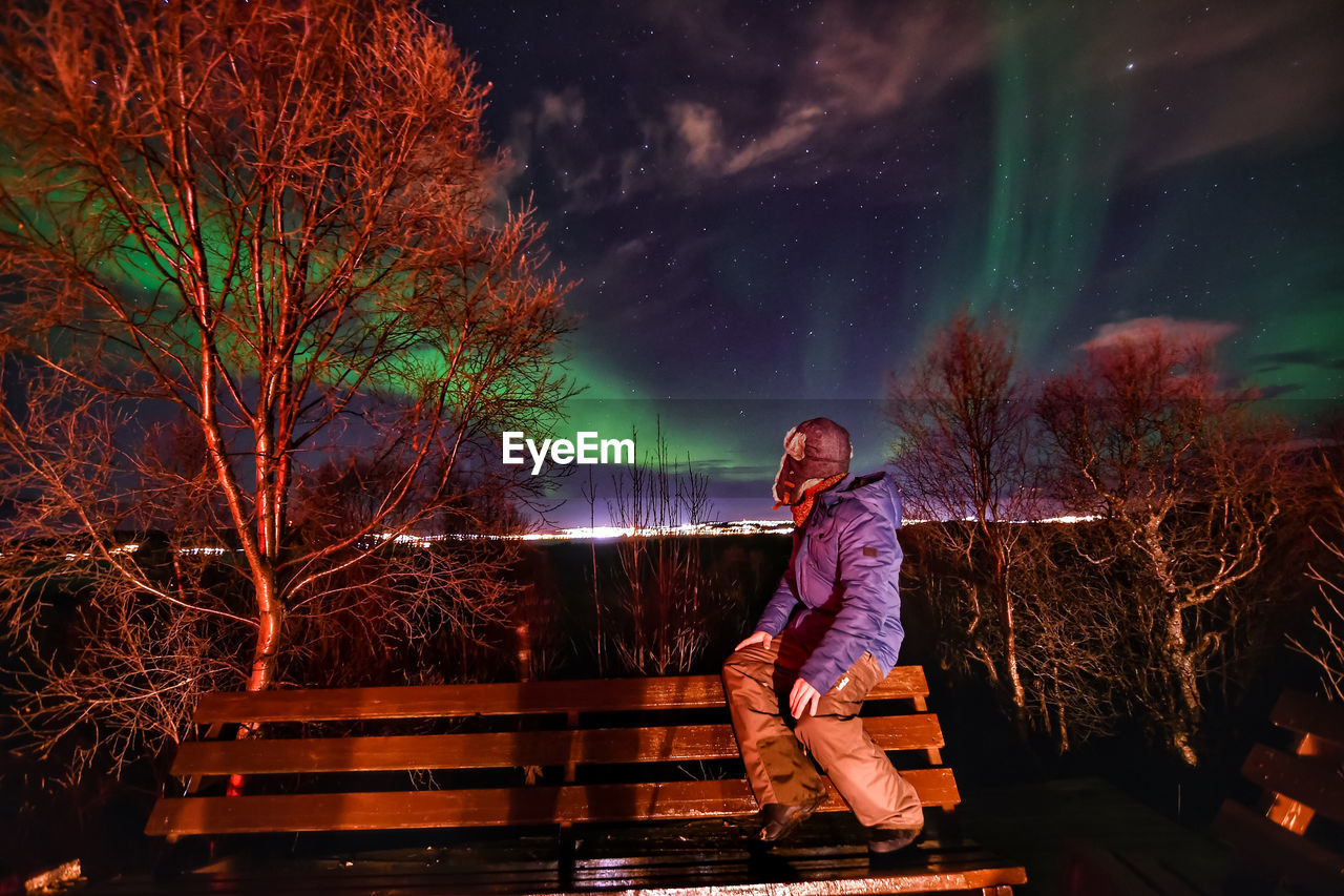 Side View Of Person Sitting On Bench Against Northern Lights At Night