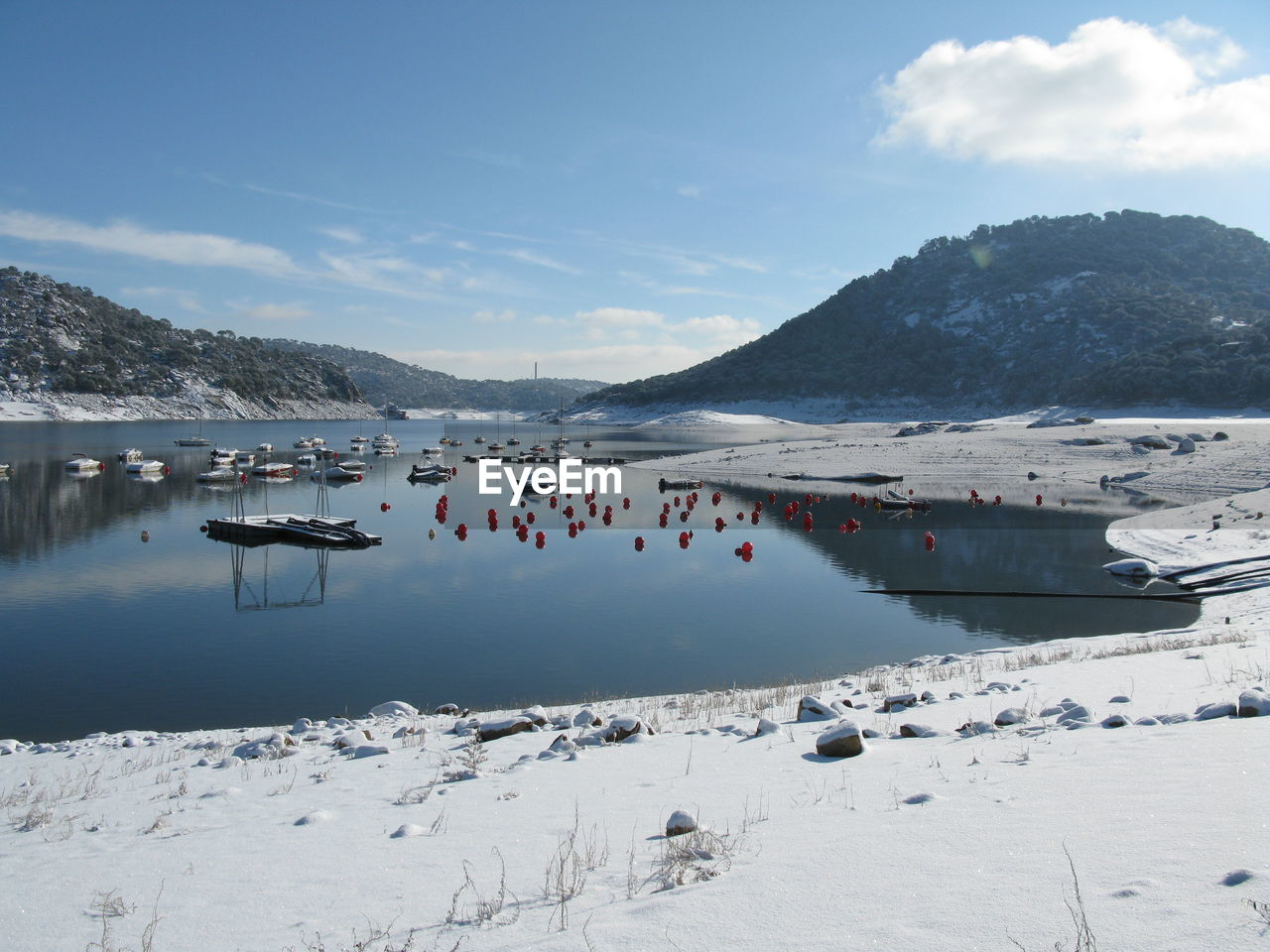 Scenic View Of River By Snow Covered Mountain Against Clear Blue Sky