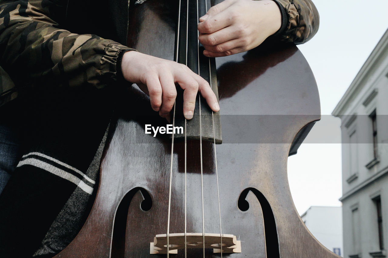 Midsection of man playing cello