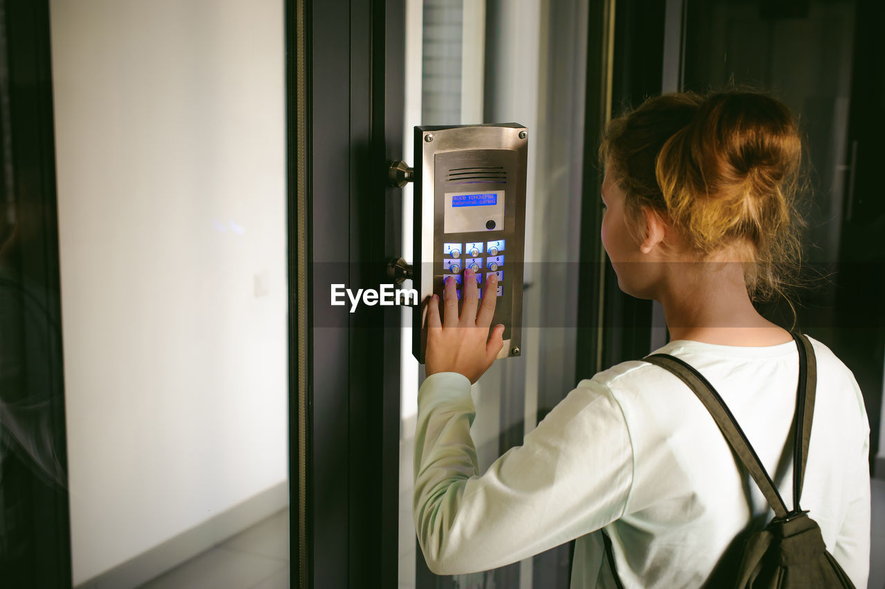 Side View Of Young Woman Using Intercom