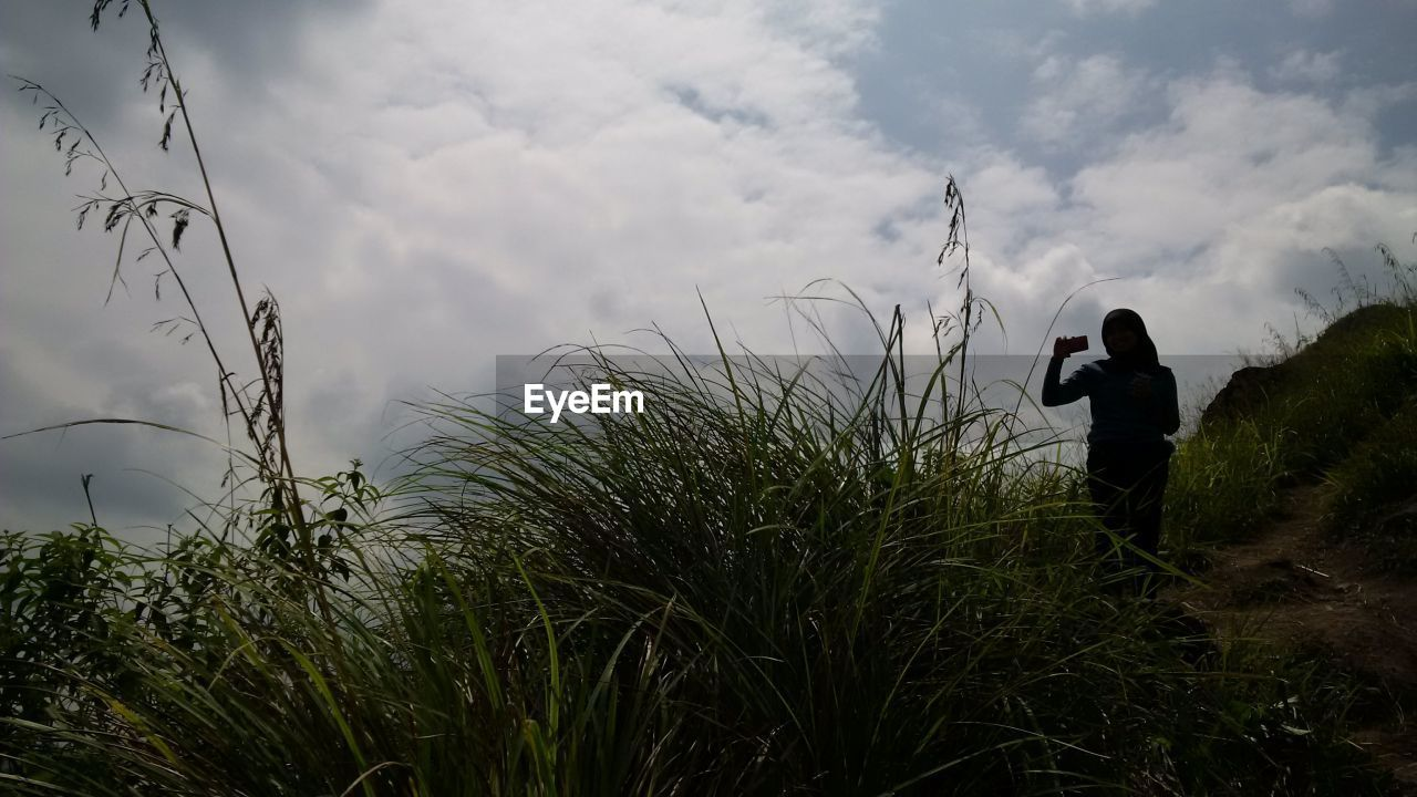 cloud - sky, one person, sky, rear view, real people, standing, leisure activity, growth, outdoors, nature, silhouette, grass, men, plant, day, lifestyles, full length, beauty in nature, people