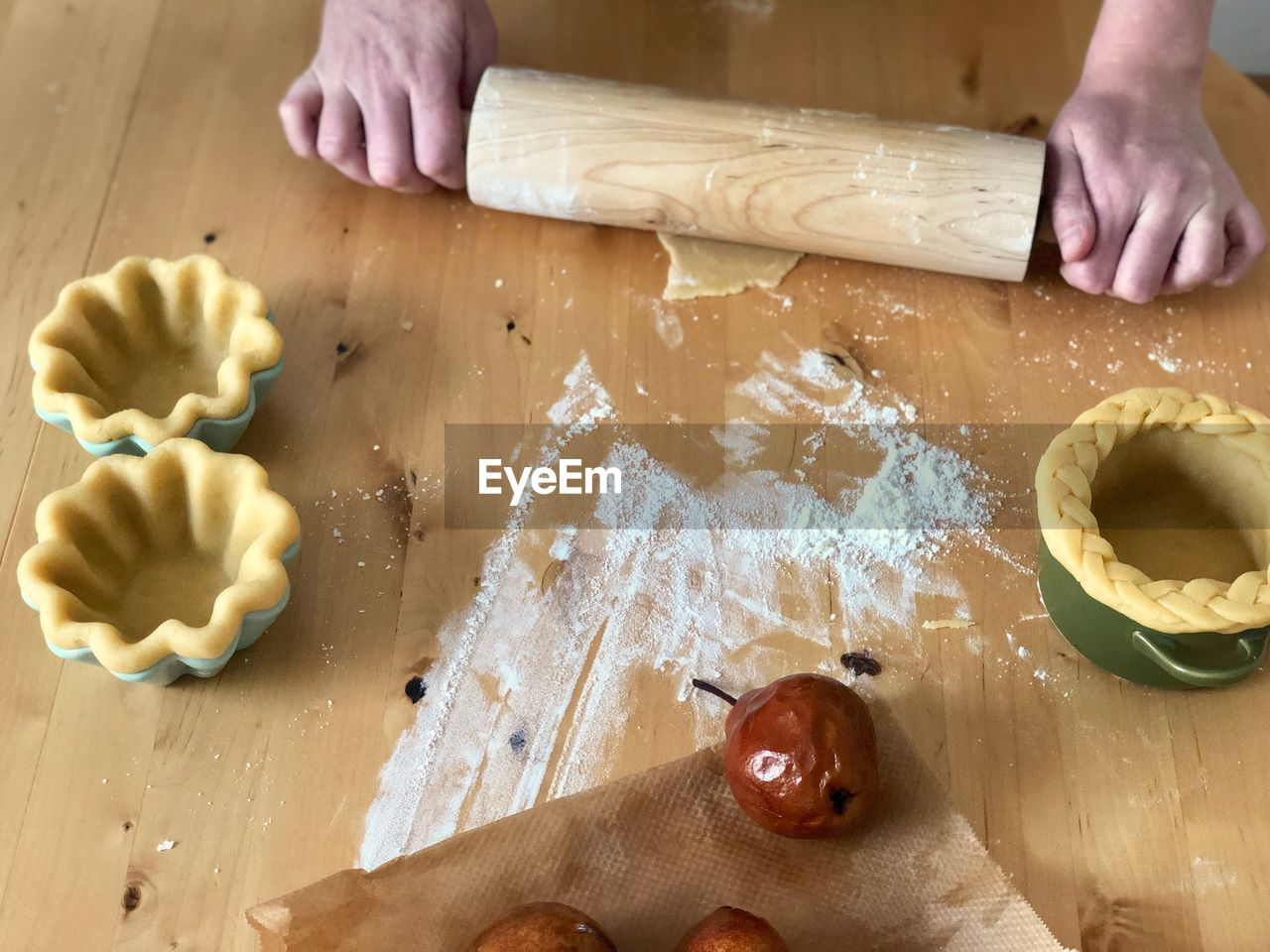 human hand, food and drink, food, hand, one person, human body part, table, dough, preparation, real people, indoors, preparing food, freshness, unrecognizable person, high angle view, flour, lifestyles, rolling pin, kitchen utensil, body part, finger