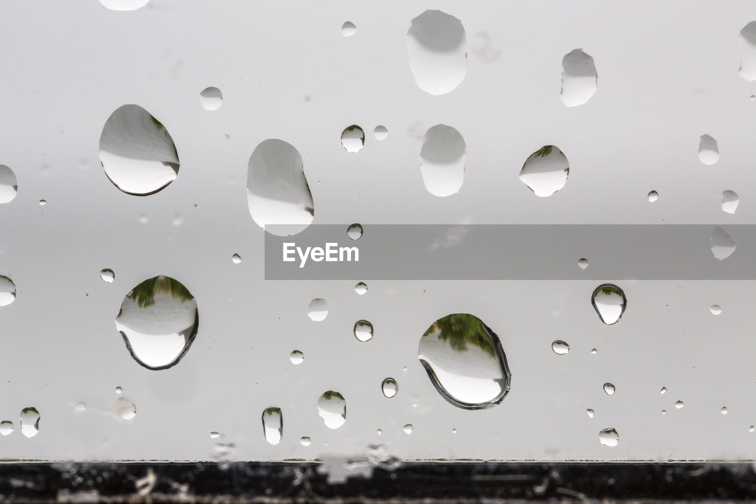 Extreme close-up of raindrops on window during rainy season