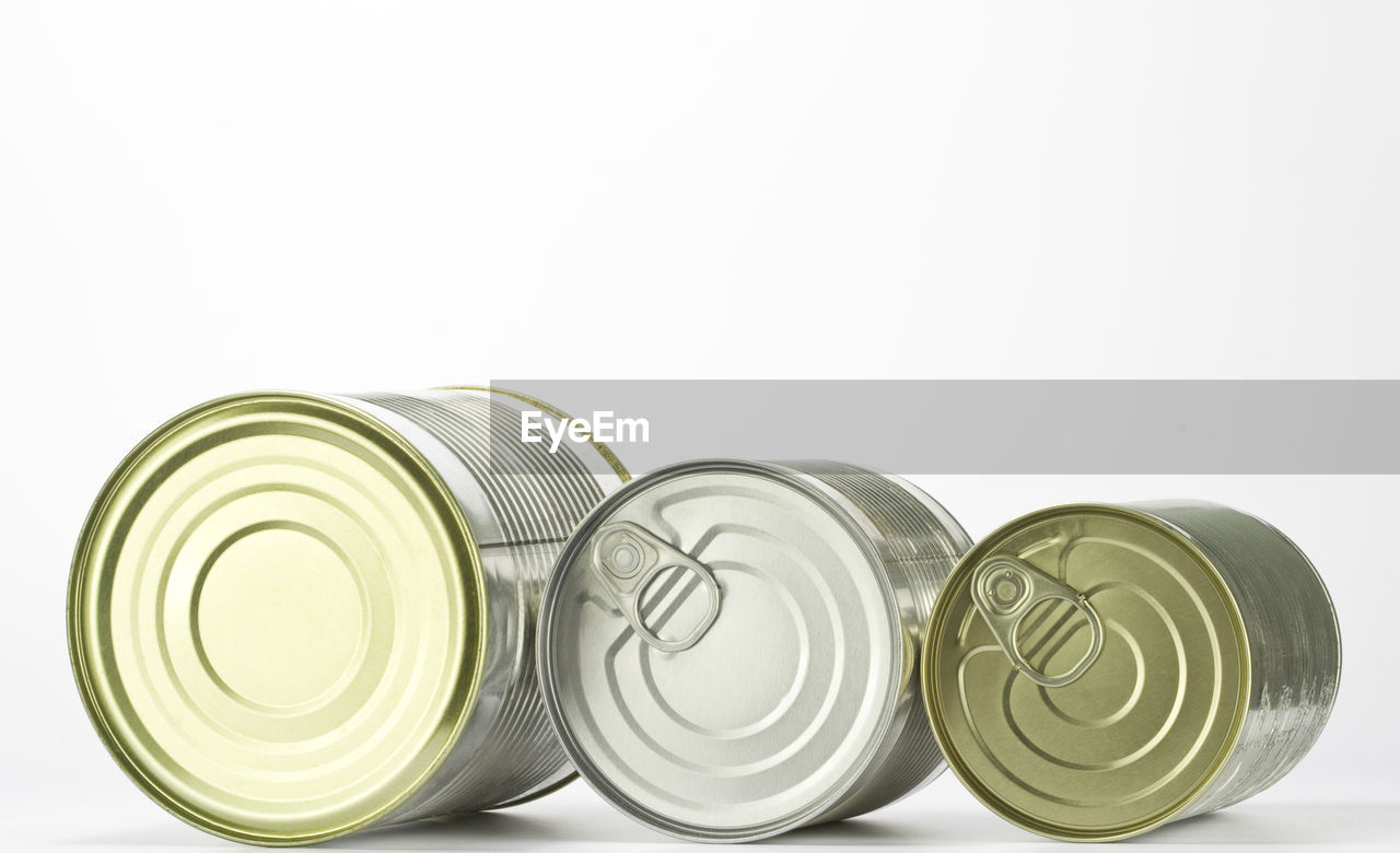 Close-Up Of Tin Cans Over White Background