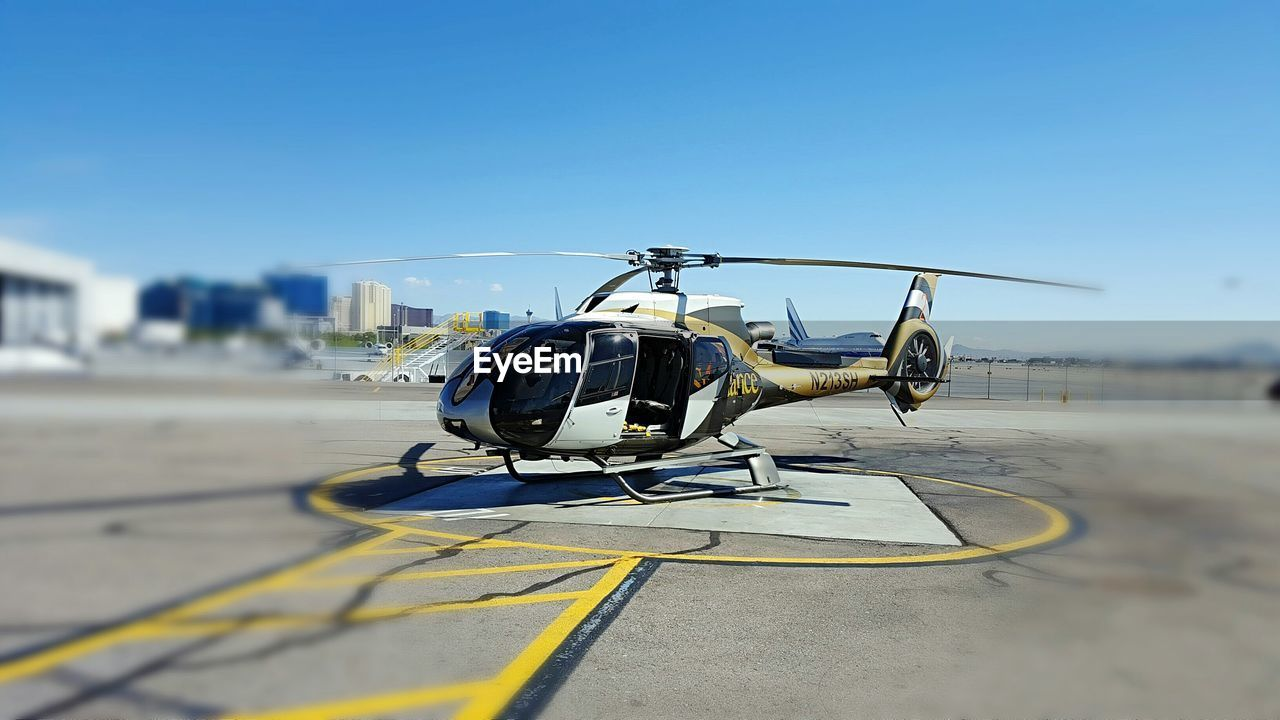 transportation, air vehicle, clear sky, mode of transport, helicopter, sky, airport runway, sunlight, outdoors, day, airplane, no people