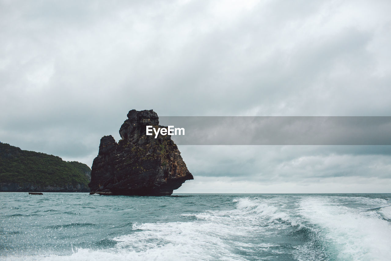 Rock Formation In Sea Against Sky