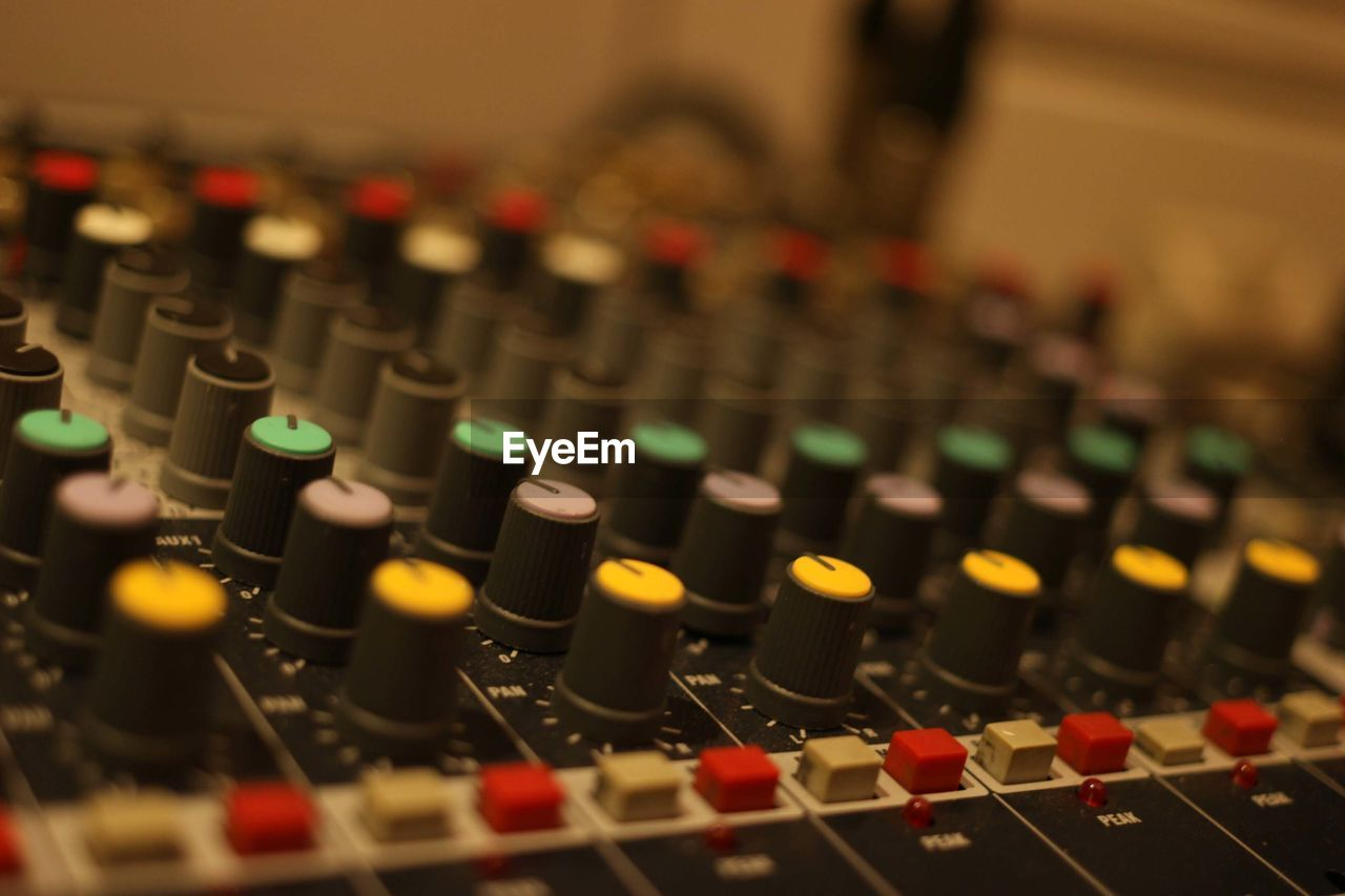 technology, audio equipment, sound mixer, arts culture and entertainment, sound recording equipment, music, control, indoors, close-up, recording studio, studio, control panel, focus on foreground, selective focus, no people, illuminated, equipment, in a row, knob, communication, mixing, push button, electrical equipment, audio electronics