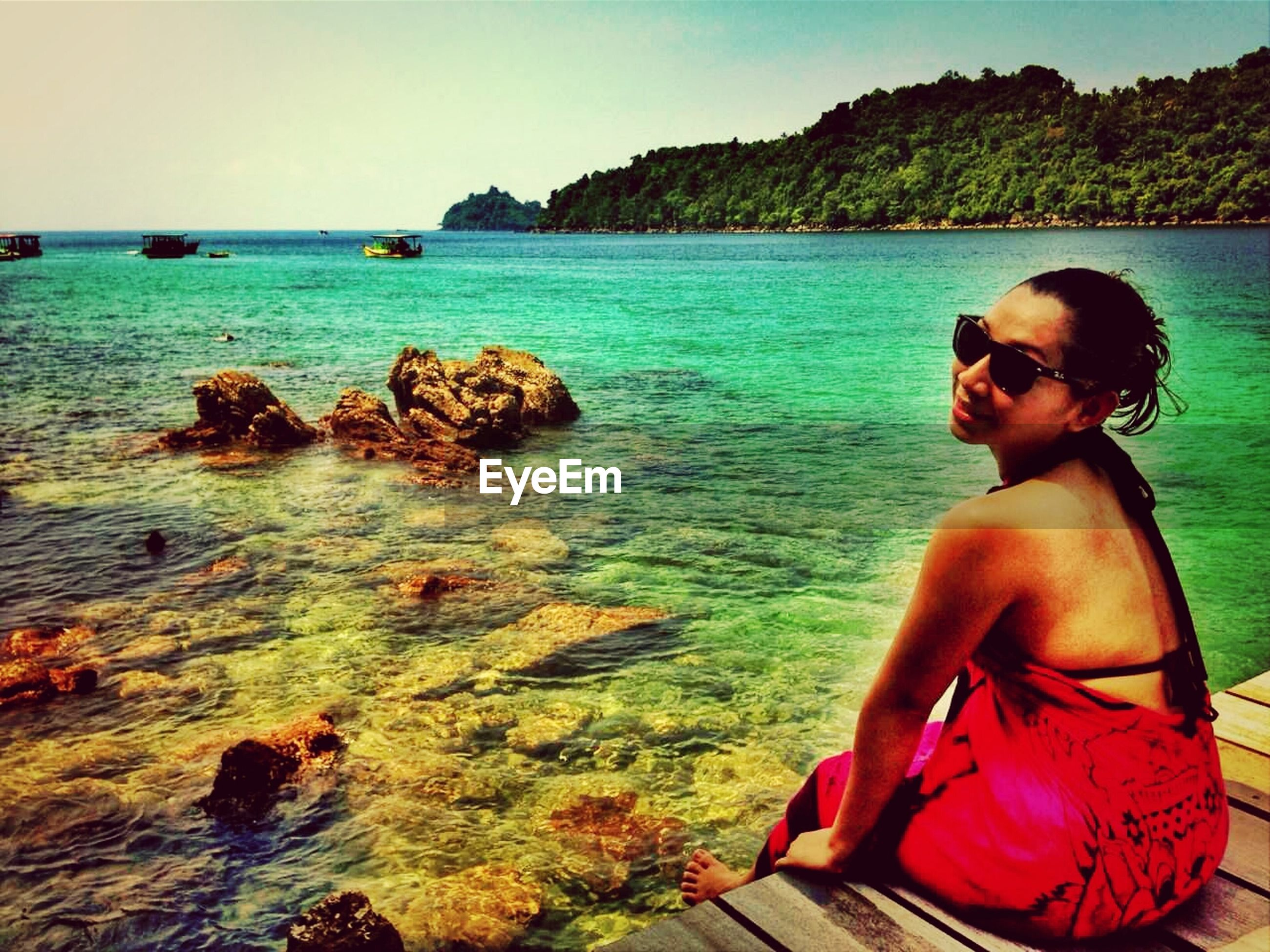water, lifestyles, young adult, leisure activity, sea, person, sitting, young women, casual clothing, sunglasses, clear sky, vacations, smiling, relaxation, waist up, three quarter length, looking at camera