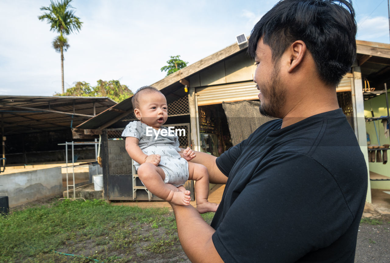 FATHER AND SON HOLDING BABY WHILE STANDING ON GROUND