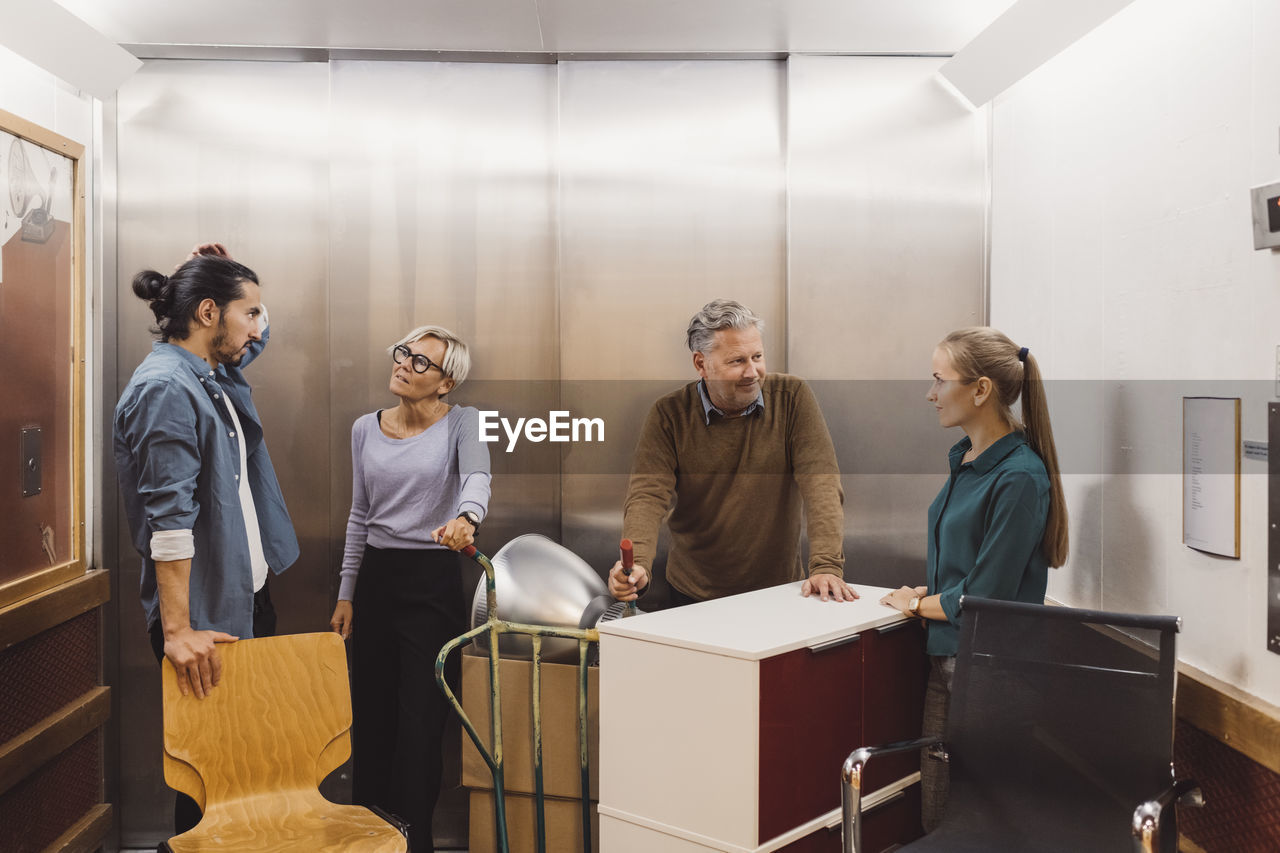 GROUP OF PEOPLE STANDING BY TABLE IN CORRIDOR