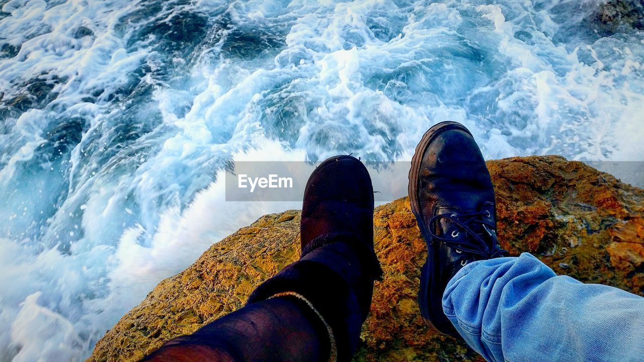 low section, personal perspective, shoe, water, real people, sea, motion, human leg, one person, human body part, body part, lifestyles, nature, sport, men, solid, wave, rock, outdoors, flowing water