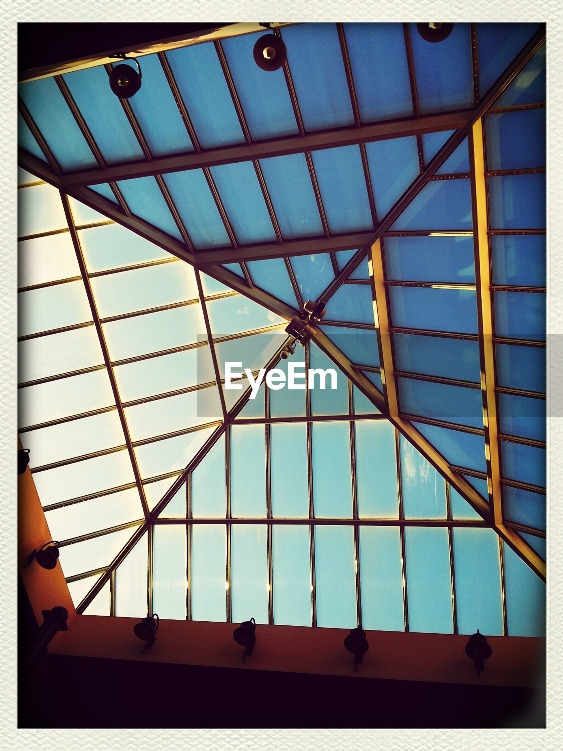 low angle view, architecture, built structure, indoors, glass - material, ceiling, pattern, transfer print, modern, geometric shape, sky, skylight, auto post production filter, building exterior, transparent, architectural feature, grid, window, glass, day