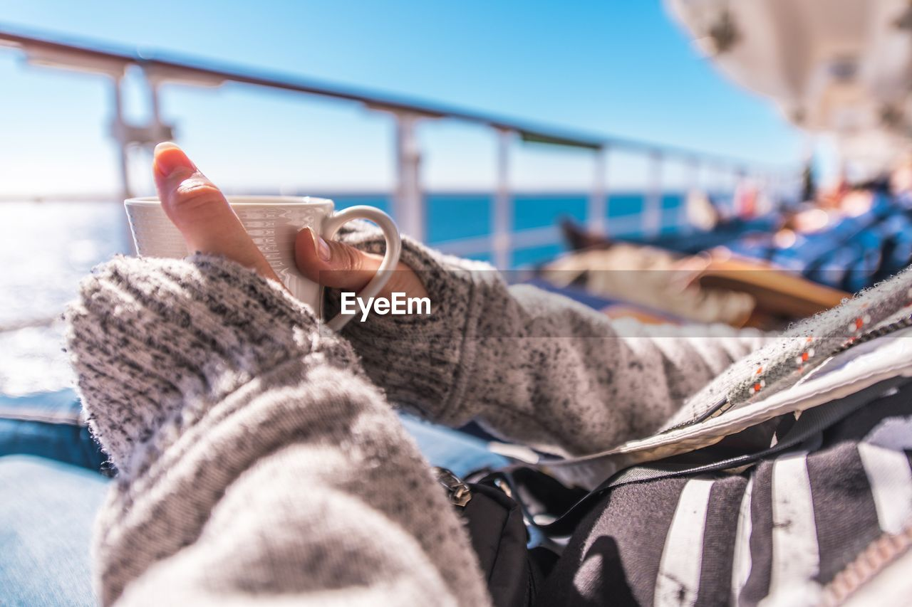 Midsection Of Woman Holding Cup While Relaxing On Cruise Ship