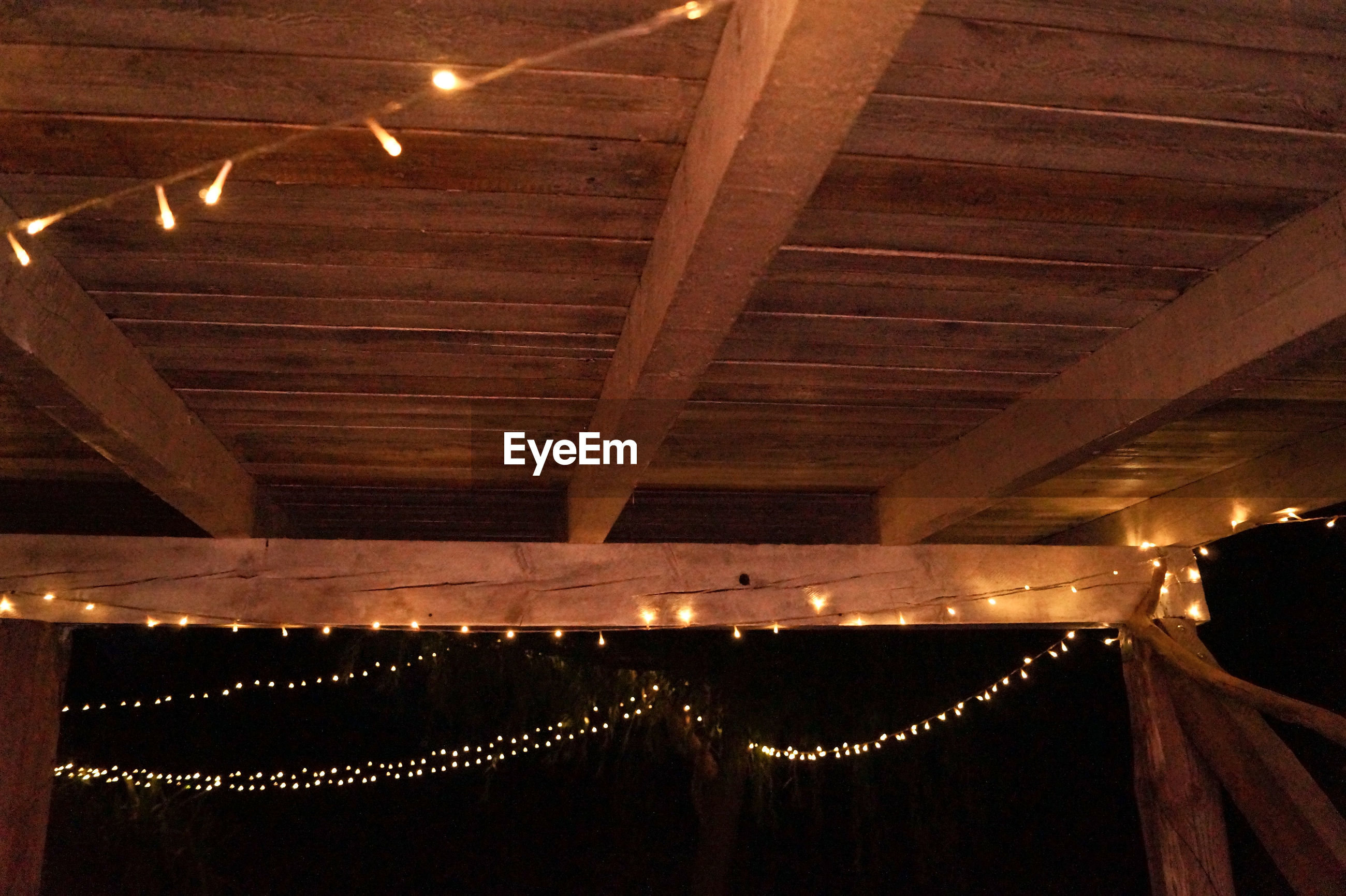 Low angle view of illuminated fairy light decoration on wooden ceiling at night