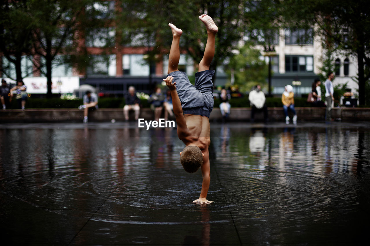 Full length of boy doing handstand in city during rainy season