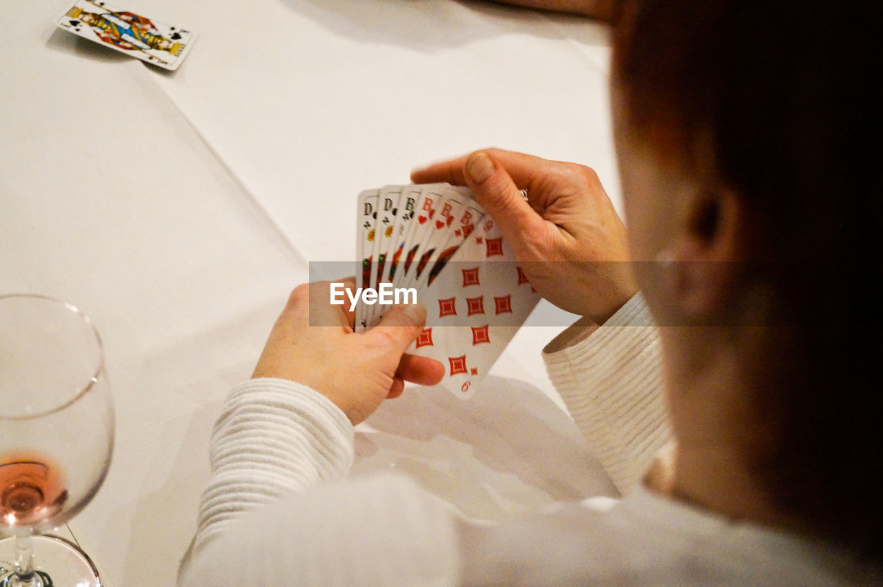 playing, indoors, leisure games, human hand, leisure activity, one person, real people, cards, high angle view, gambling, human body part, competition, chance, close-up, day, people