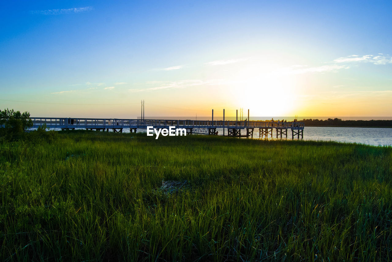 Grassy Field And Pier At Lake Against Sky During Sunset