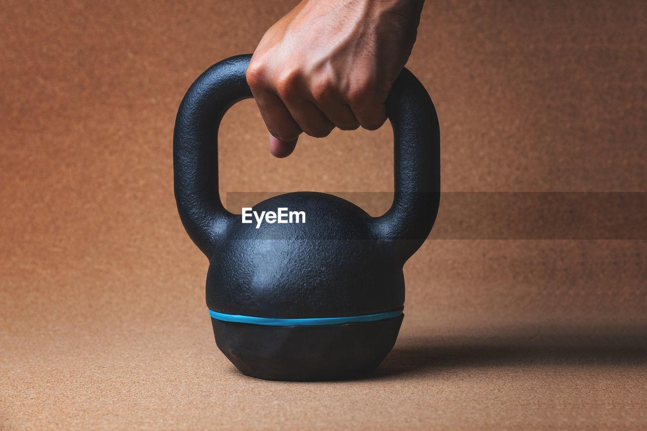 Cropped Hand Holding Kettlebell In Gym