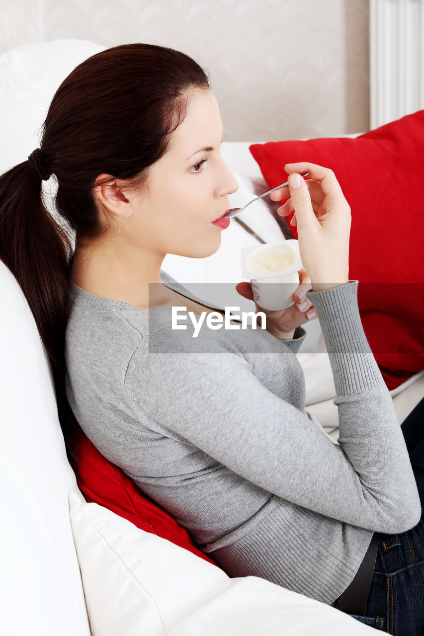 High Angle View Of Young Woman Eating Ice Cream While Sitting On Sofa At Home