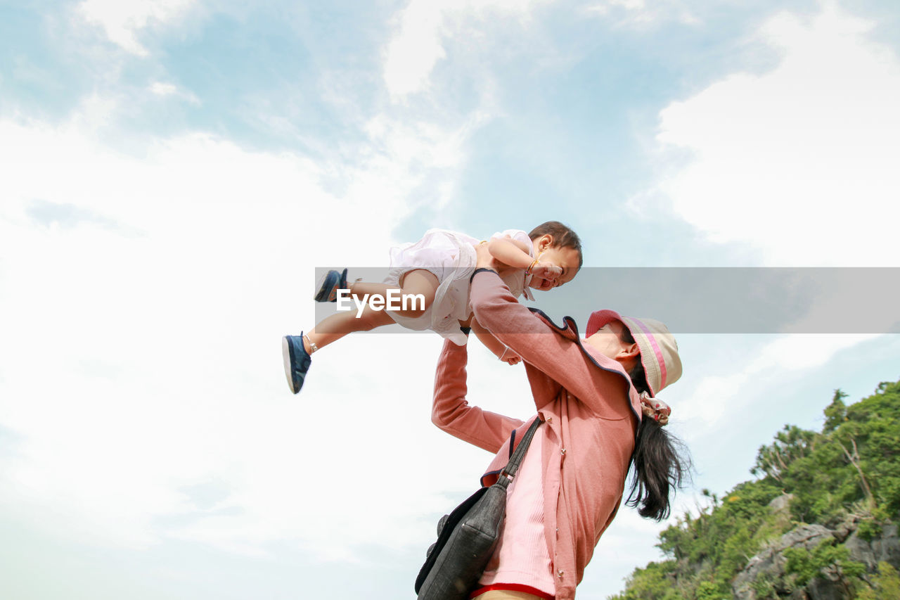 Low Angle View Of Mother Carrying Daughter Against Sky