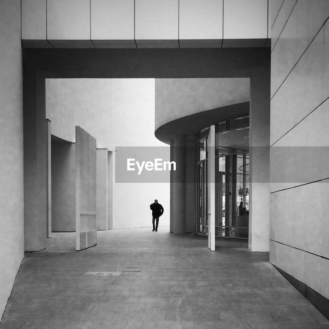 Man Walking In Building Corridor