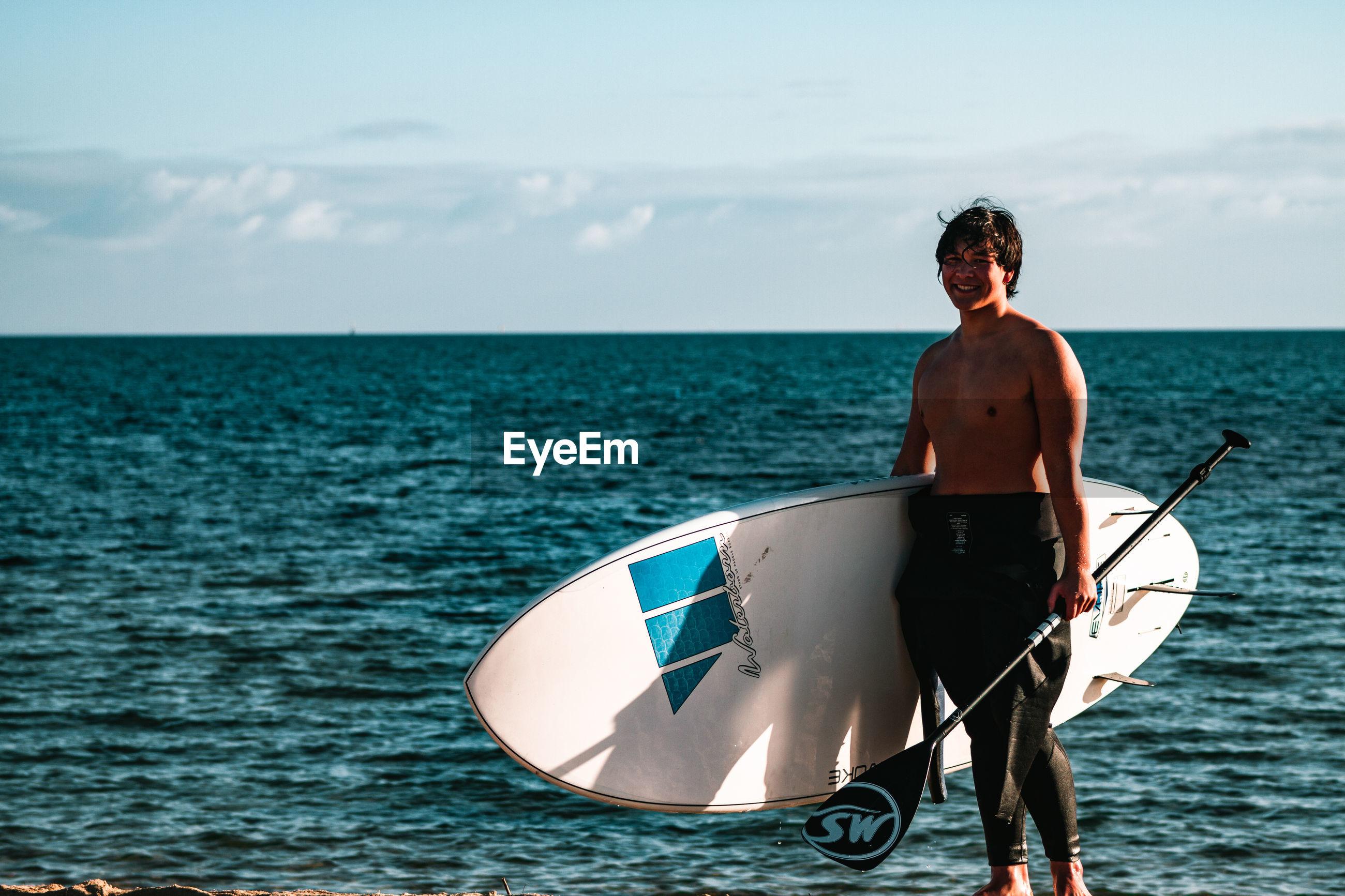 MAN STANDING IN BOAT AGAINST SEA
