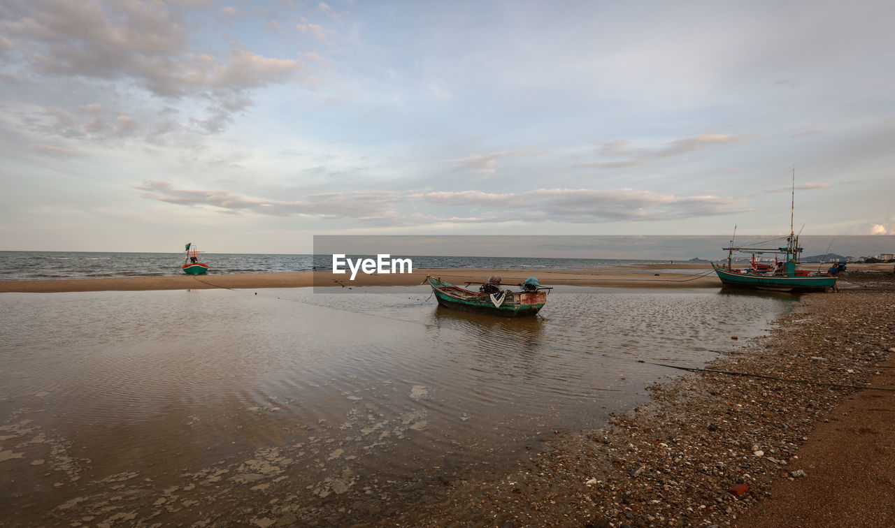 nautical vessel, water, transportation, sky, cloud - sky, mode of transportation, sea, beauty in nature, scenics - nature, beach, horizon, nature, tranquility, horizon over water, land, moored, tranquil scene, day, non-urban scene, outdoors, anchored, fishing boat