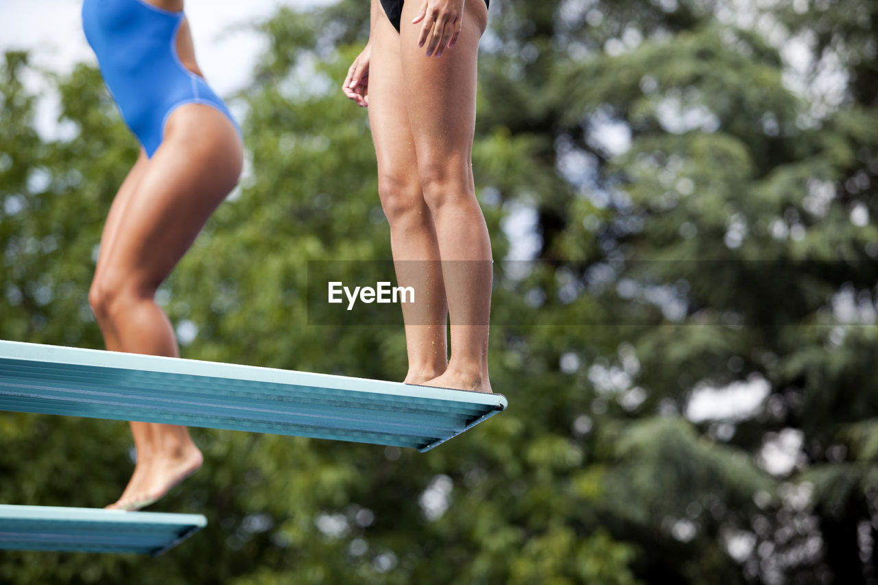 Low Section Of Man Jumping Over Diving Board
