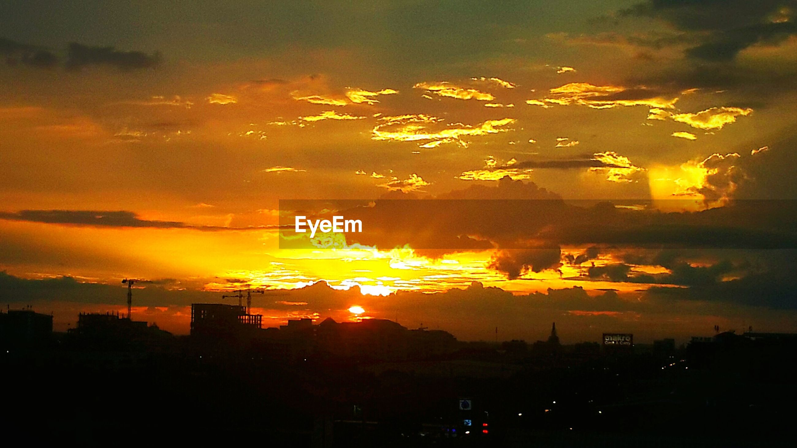 sunset, orange color, built structure, architecture, city, building exterior, cloud - sky, silhouette, scenics, sky, sun, beauty in nature, cityscape, romantic sky, outdoors, sunbeam, dramatic sky, urban skyline, majestic, atmospheric mood, atmosphere, cloudy, nature, city life, tranquil scene, tranquility, vibrant color, storm cloud, tall - high, outline, cloudscape