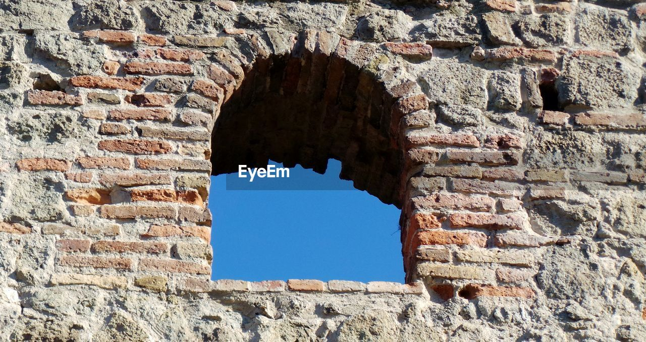 architecture, built structure, arch, window, hole, brick wall, low angle view, building exterior, damaged, day, old ruin, history, no people, bad condition, outdoors, clear sky, ancient civilization, sky