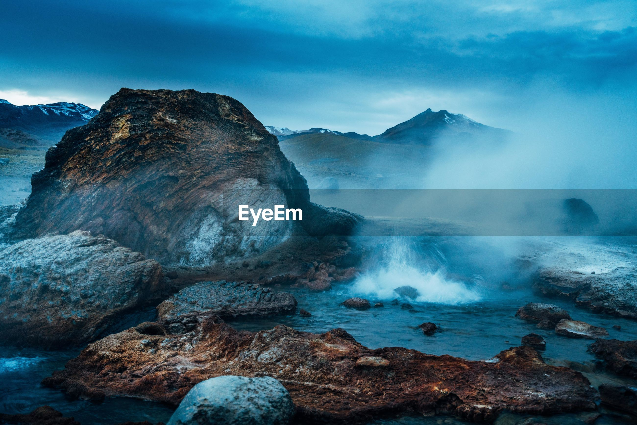 Scenic view of volcanic landscape against cloudy sky