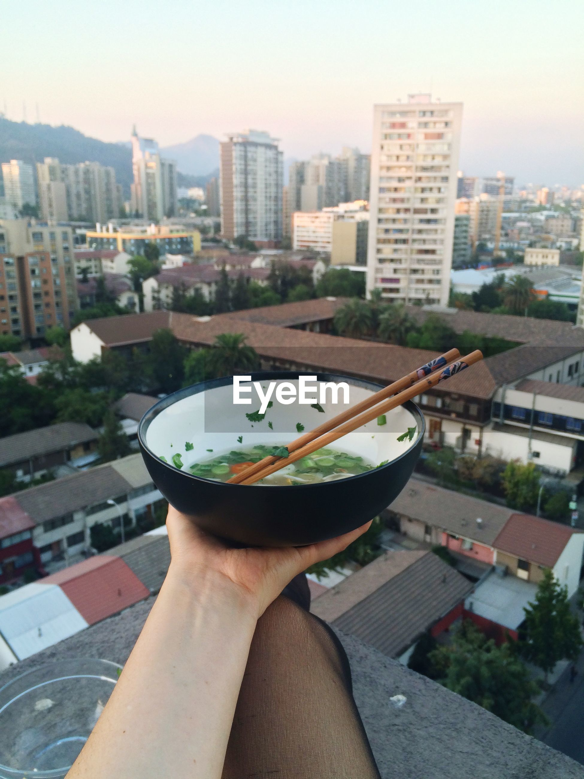Cropped image of woman holding bowl of soup against cityscape