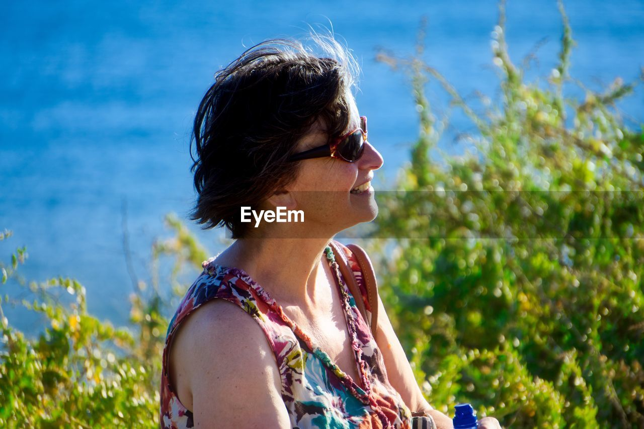 Woman Wearing Sunglasses Against Sea On Sunny Day