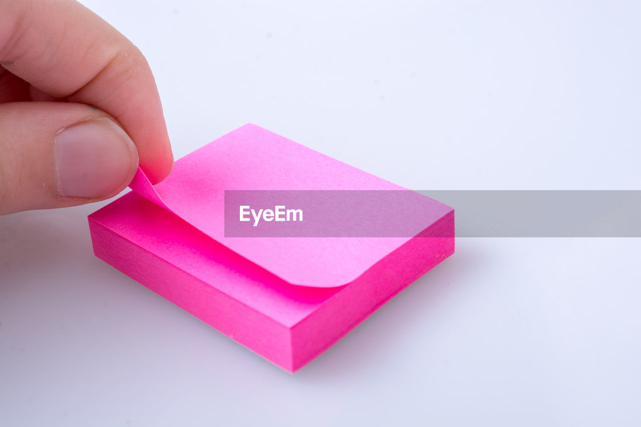 Close-Up Of Hand Holding Adhesive Note On Table