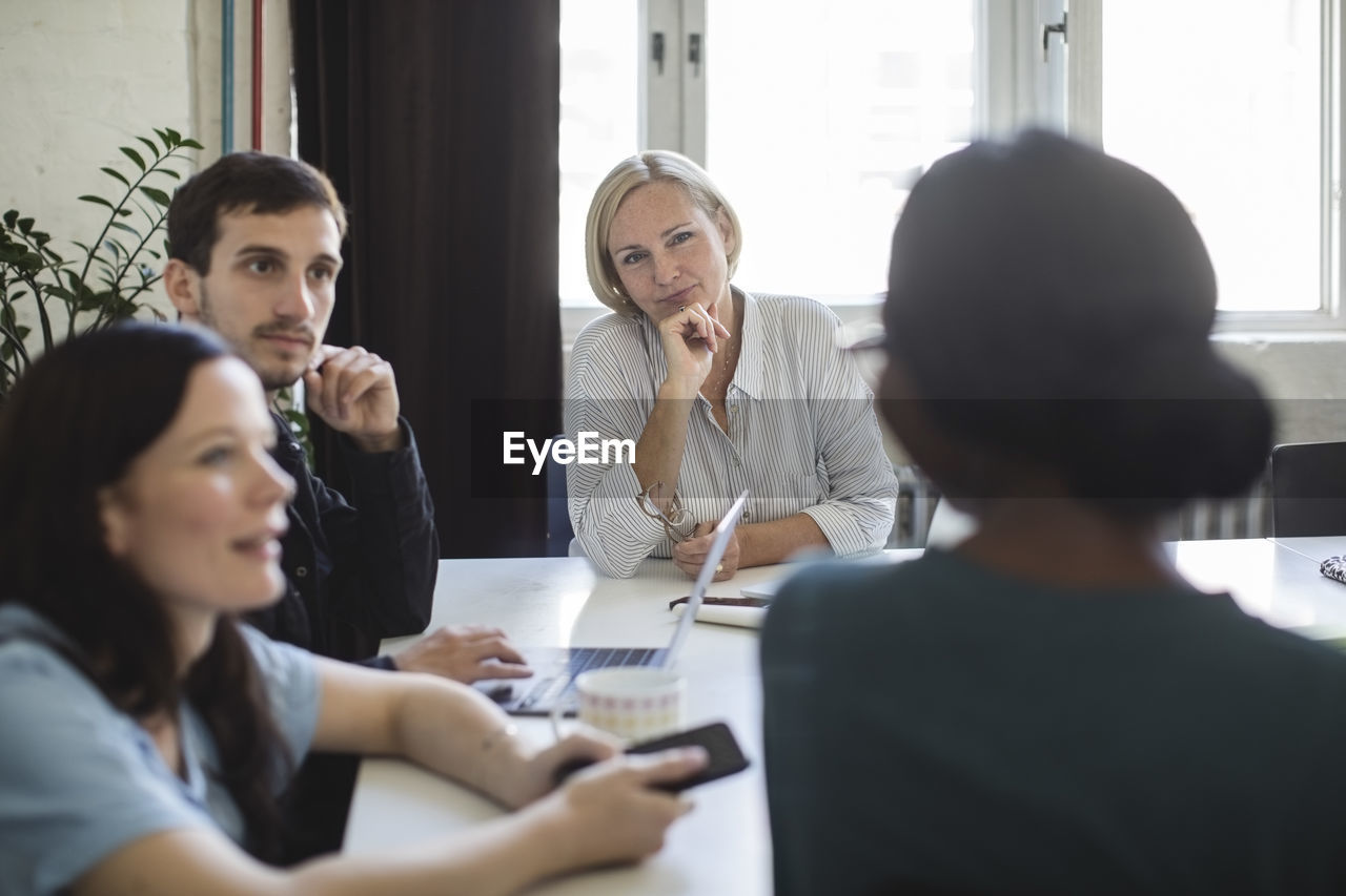 women, communication, sitting, adult, table, group of people, indoors, young adult, office, real people, business, selective focus, meeting, men, females, business meeting, people, business person, businesswoman, teamwork, coworker, brainstorming, using laptop