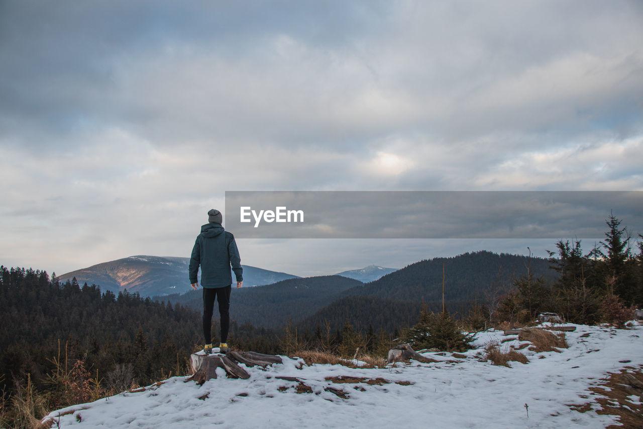 REAR VIEW OF MAN STANDING ON SNOW COVERED MOUNTAIN