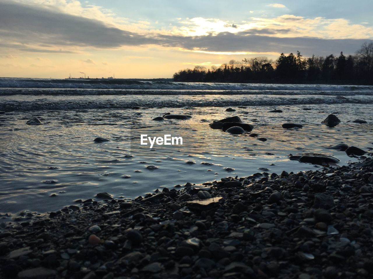 Scenic view of rocky shore against sky at sunset
