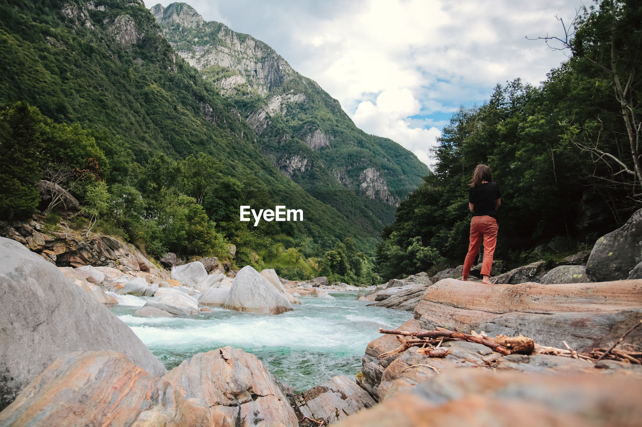 mountain, nature, real people, one person, sky, beauty in nature, rock - object, standing, adventure, day, outdoors, landscape, leisure activity, tree, tranquility, full length, scenics, women, water, young adult, people