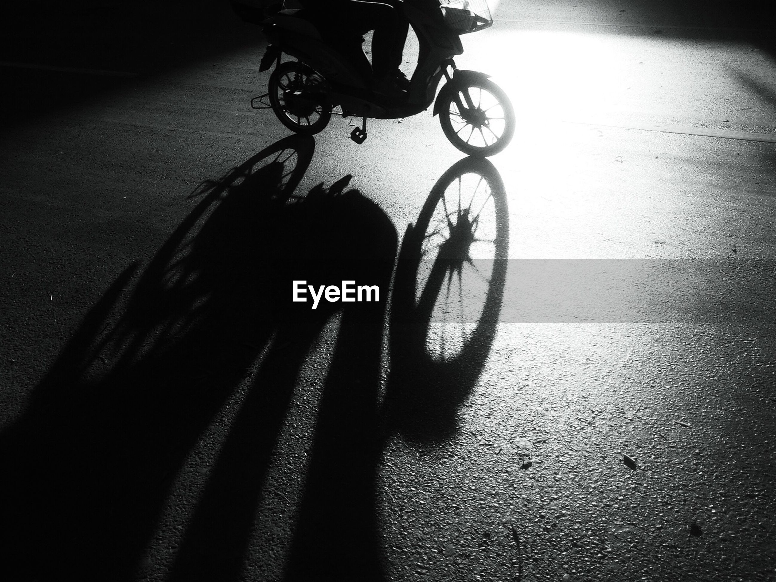 bicycle, transportation, land vehicle, mode of transport, low section, shadow, street, riding, person, part of, road, sunlight, high angle view, indoors, unrecognizable person, stationary, cycling