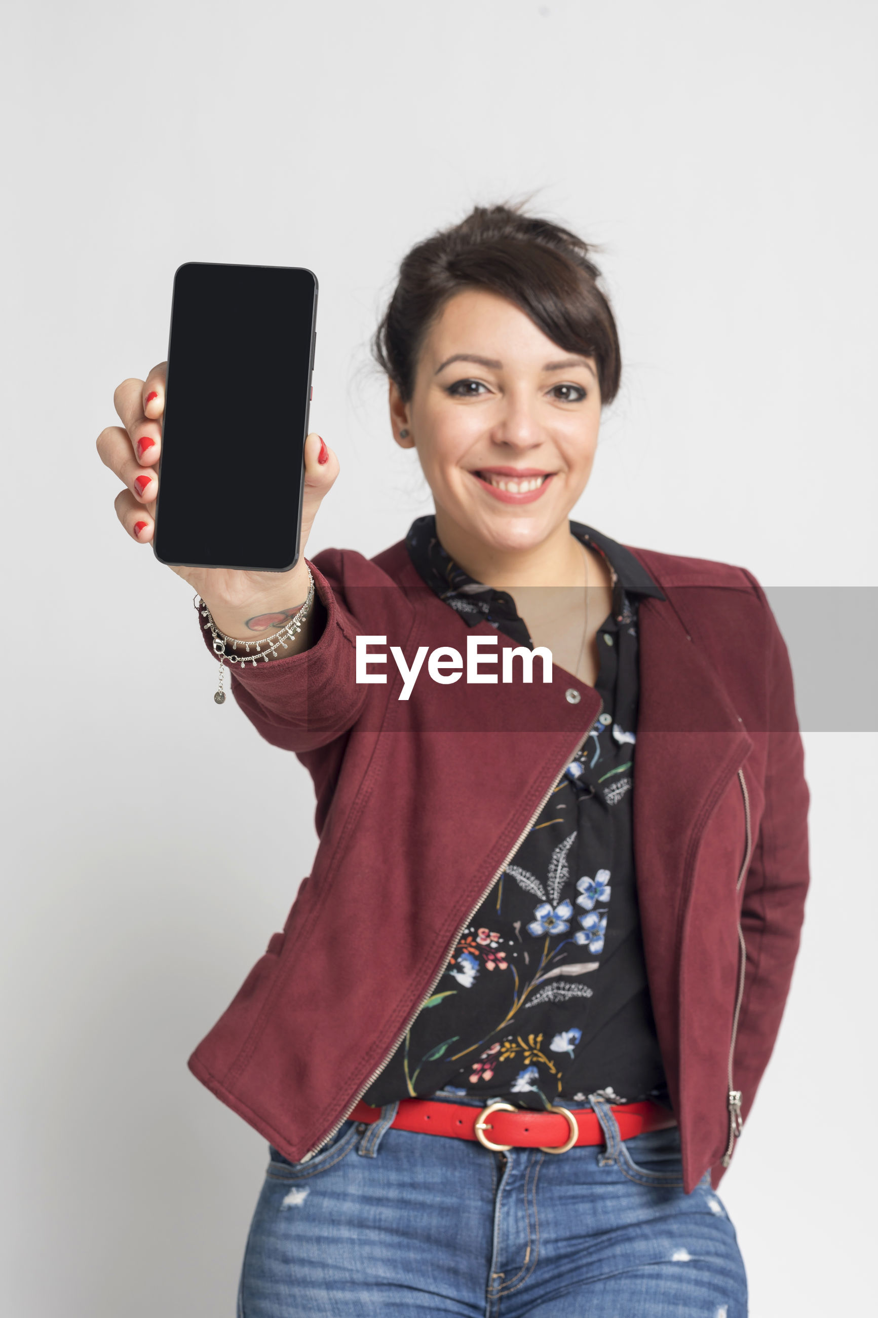 Portrait of smiling woman holding mobile phone while standing against white background