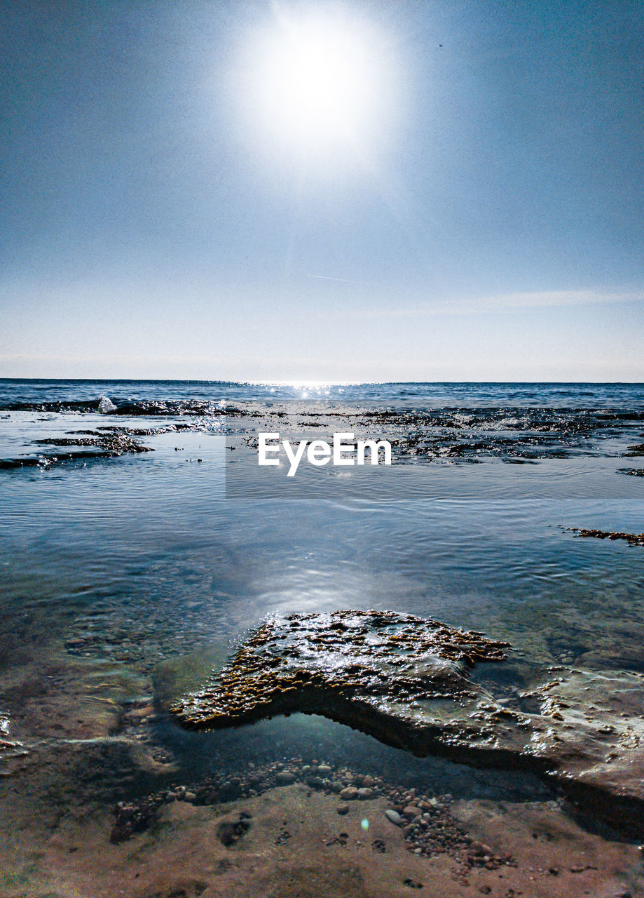 sky, sea, water, beach, land, scenics - nature, beauty in nature, tranquility, horizon over water, horizon, nature, tranquil scene, sunlight, day, no people, sun, idyllic, clear sky, motion, outdoors, lens flare