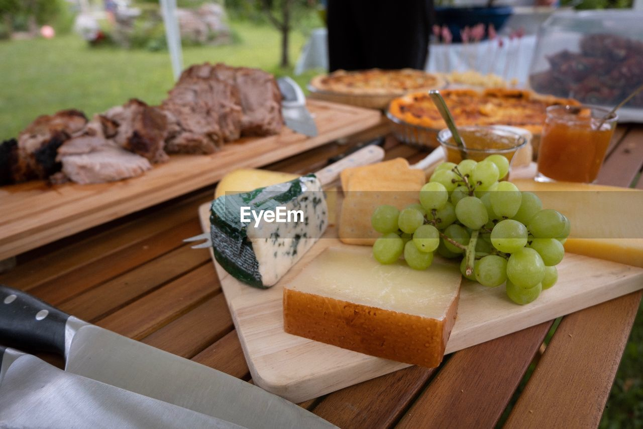 food and drink, food, freshness, healthy eating, wellbeing, wood - material, no people, table, cutting board, fruit, focus on foreground, indoors, close-up, still life, cheese, high angle view, selective focus, dairy product, grape, kitchen knife, tray, snack