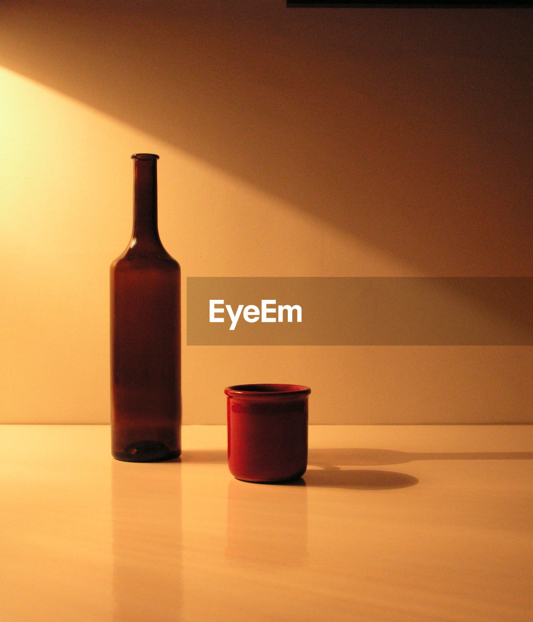 indoors, table, still life, bottle, container, no people, close-up, shadow, red, copy space, two objects, reflection, orange color, beauty product, glass - material, wall - building feature, simplicity, food and drink, lid, beauty
