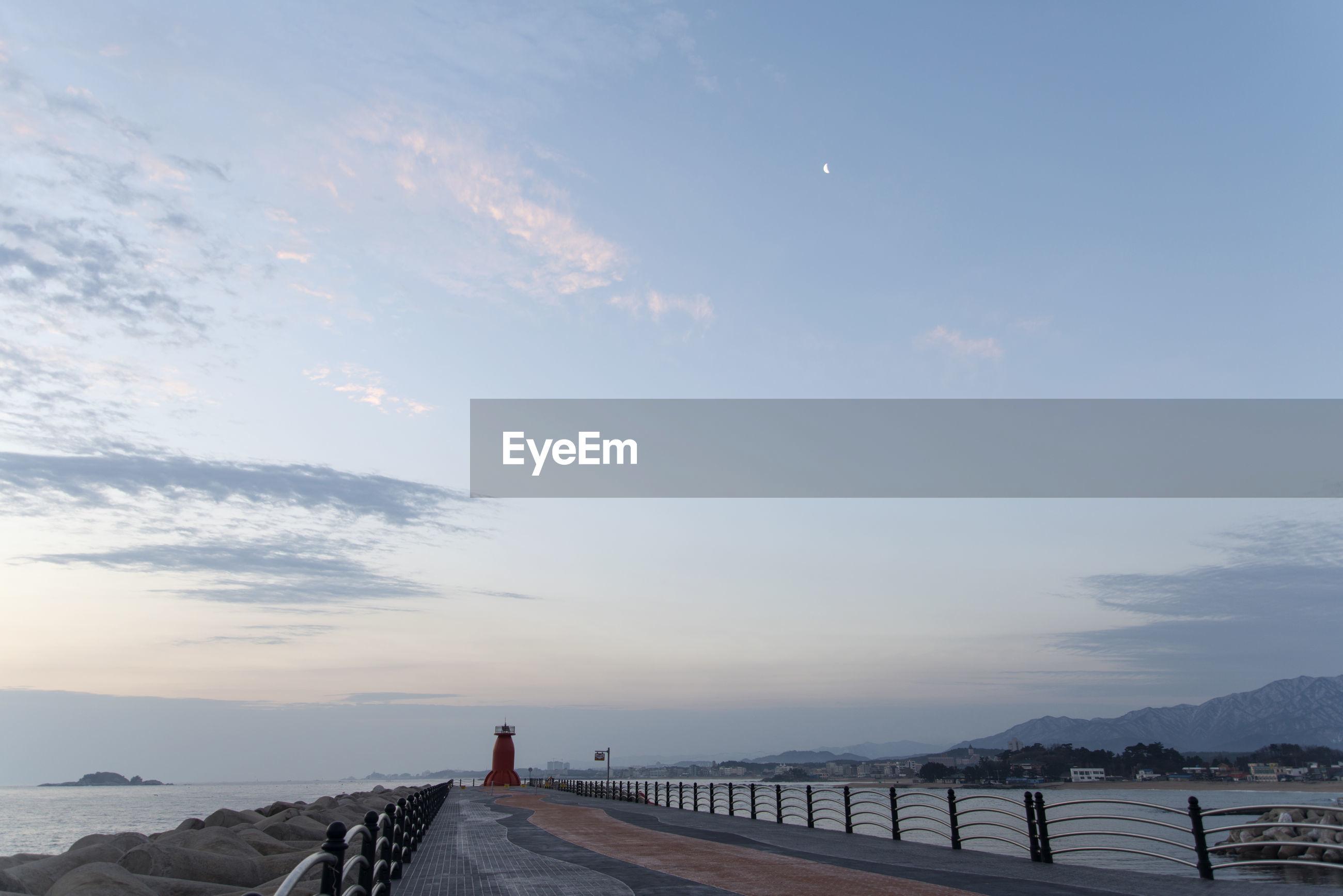 Pier in sea against sky during sunrise