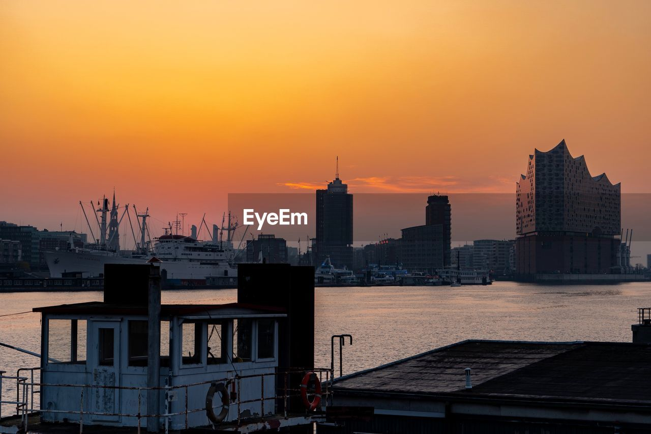 architecture, building exterior, built structure, sunset, sky, city, building, water, orange color, tall - high, nature, cityscape, tower, no people, travel destinations, office building exterior, travel, urban skyline, skyscraper, outdoors, modern, spire, financial district, construction equipment