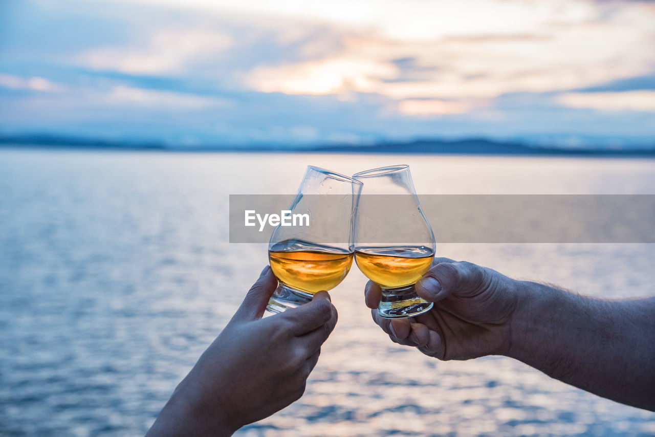 Close-Up Of Hands Toasting Glasses Against The Lake