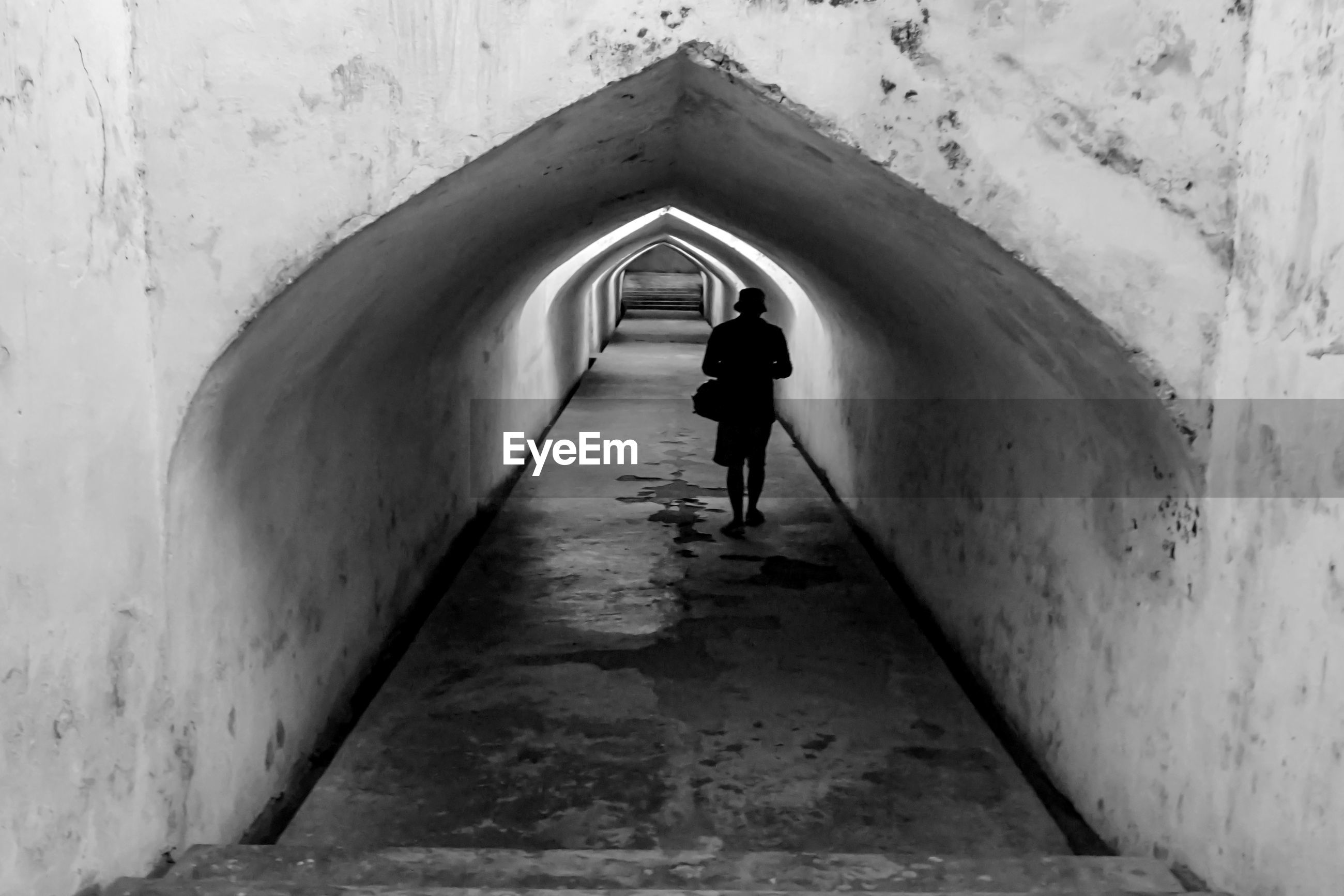 REAR VIEW OF SILHOUETTE MAN WALKING IN TUNNEL AMIDST BUILDING