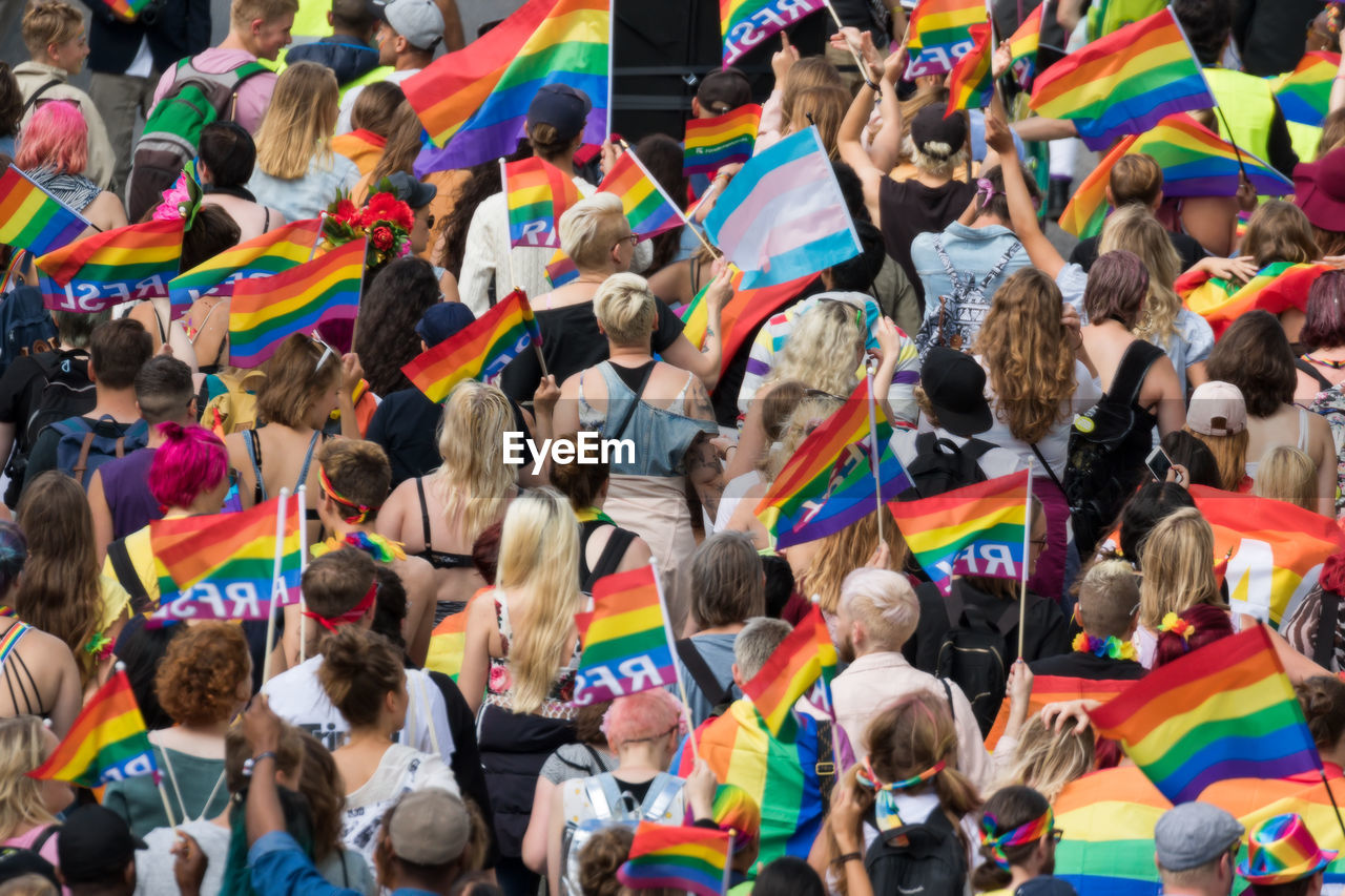 crowd, large group of people, group of people, real people, men, women, high angle view, togetherness, adult, day, multi colored, flag, unity, mixed age range, patriotism, human arm, emotion, arms raised, fan - enthusiast, spectator, human limb, excitement