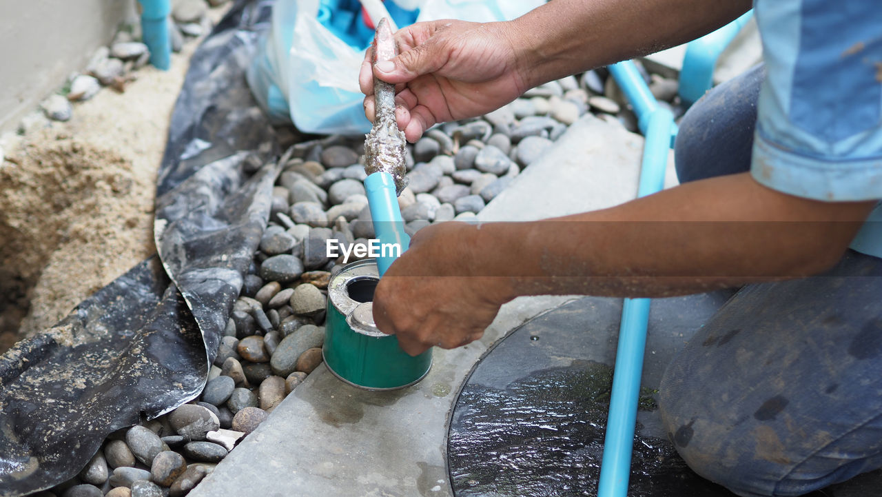 human hand, hand, real people, one person, holding, human body part, solid, day, stone - object, men, working, water, preparation, outdoors, focus on foreground, nature, rock, occupation, flowing water